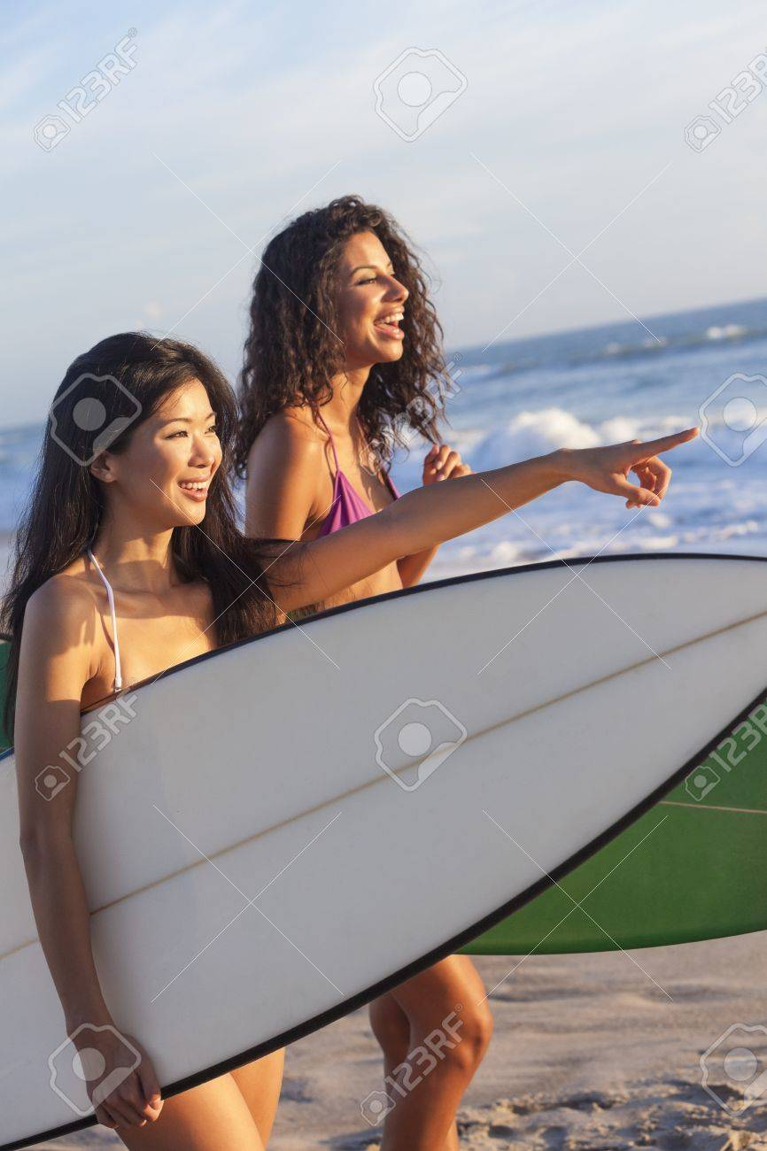 Beautiful young women surfer girls in bikinis with surfboards on a beach at sunset or sunrise Stock Photo - 15691421