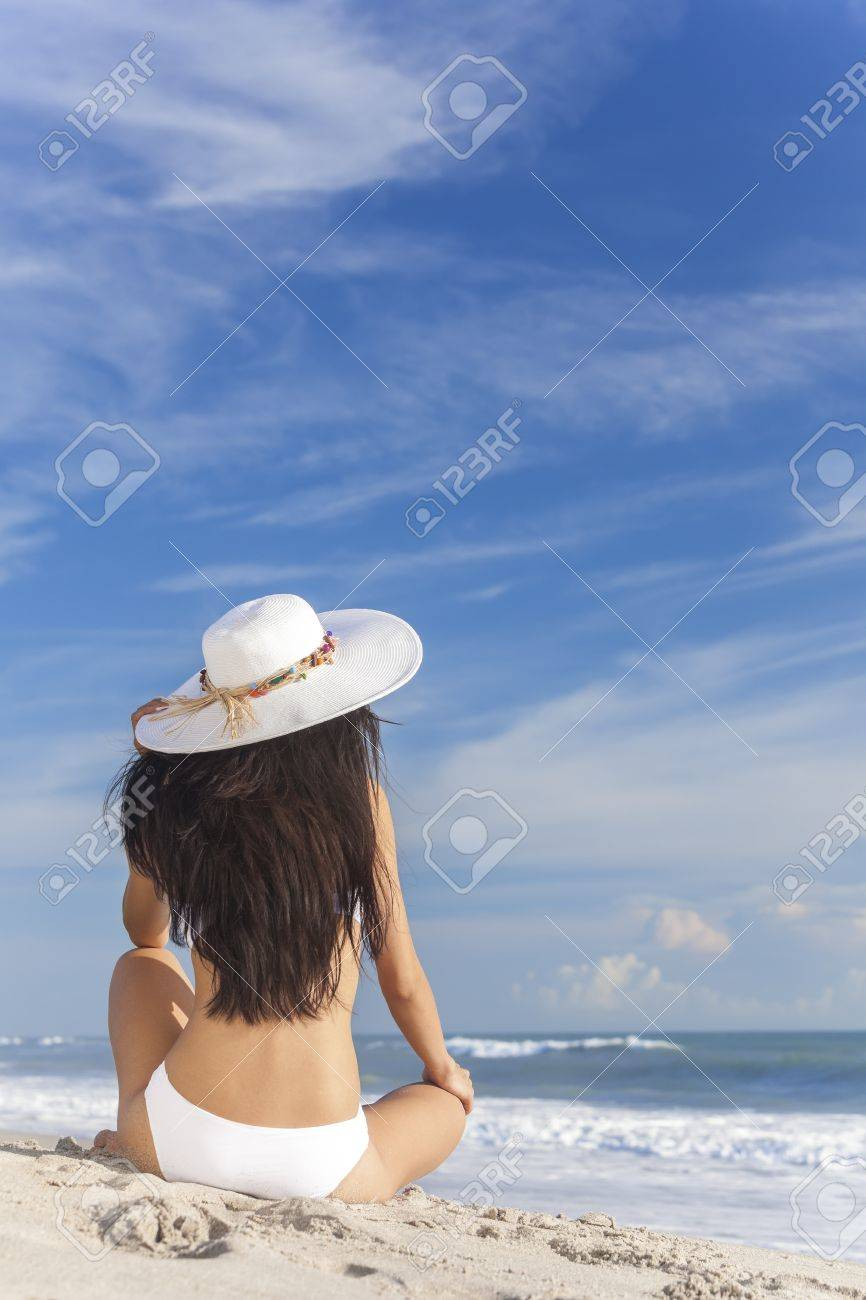 A sexy young brunette woman or girl wearing a white bikini and sun hat sitting on a deserted tropical beach with a blue sky Stock Photo - 15691416