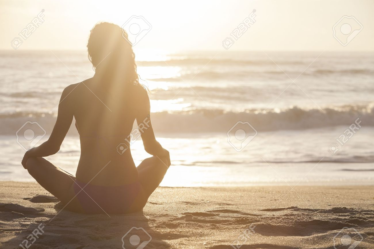 A relaxed sexy young brunette woman or girl wearing a bikini sitting on a deserted tropical beach at sunset or sunrise Stock Photo - 15896078