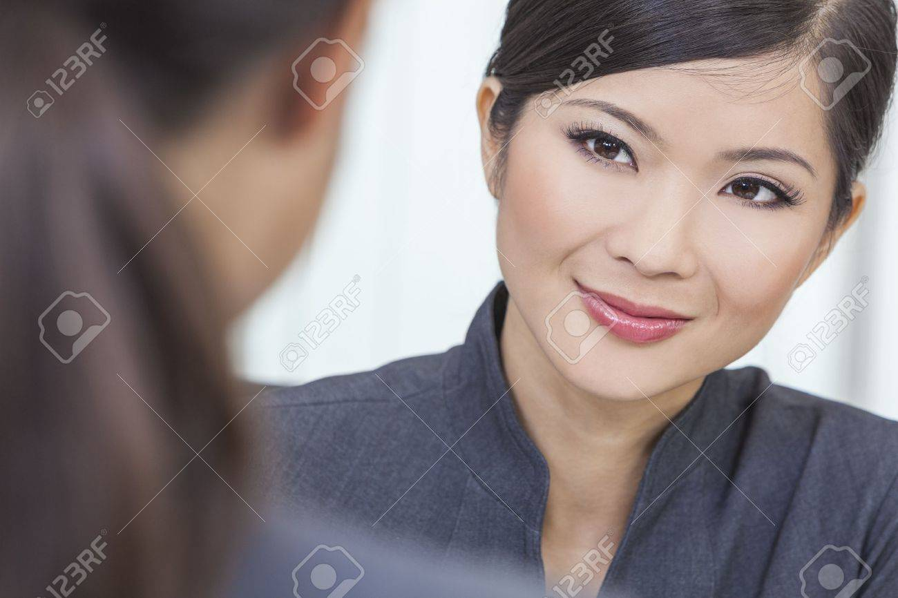 Portrait of a beautiful young Asian Chinese woman or businesswoman in office meeting with female colleague - 15941673