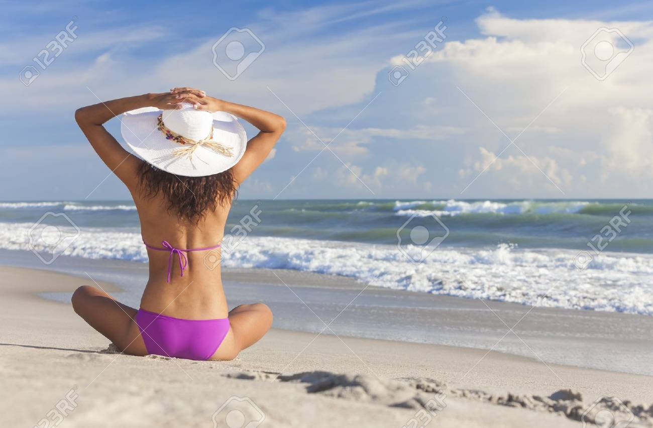A sexy young brunette woman or girl wearing a bikini and sun hat sitting on a deserted tropical beach with a blue sky Stock Photo - 16299847