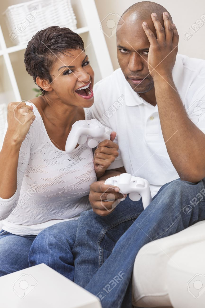 African American couple, man and woman, having fun playing video console games together  The woman has just beaten the man, she is celebrating, he is miserable Stock Photo - 16468142
