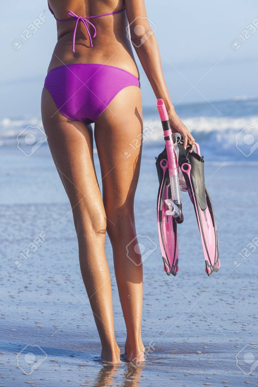 A sexy young woman or girl wearing a bikini on a deserted tropical beach with diving equipment, snorkel, mask   flippers or fins Stock Photo - 16468148