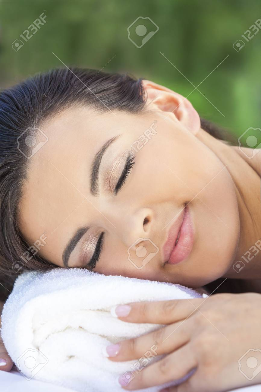Portrait of a beautiful young Latina Hispanic woman eyes closed laying down and relaxing on massage table at a health spa Stock Photo - 17165559