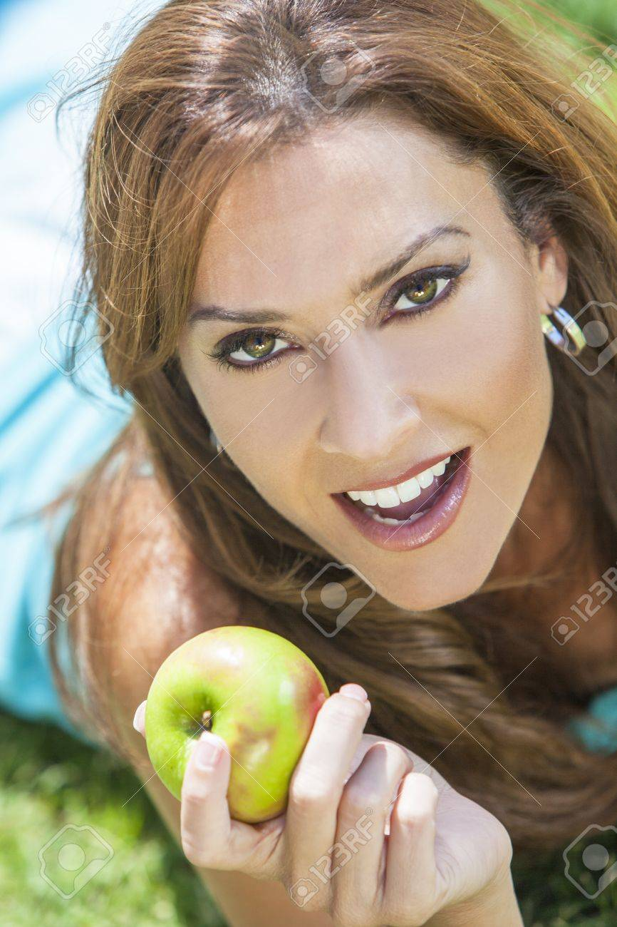 A beautiful woman in her thirties laying down outside on grass holding or eating an apple smiling with perfect teeth Stock Photo - 17165567
