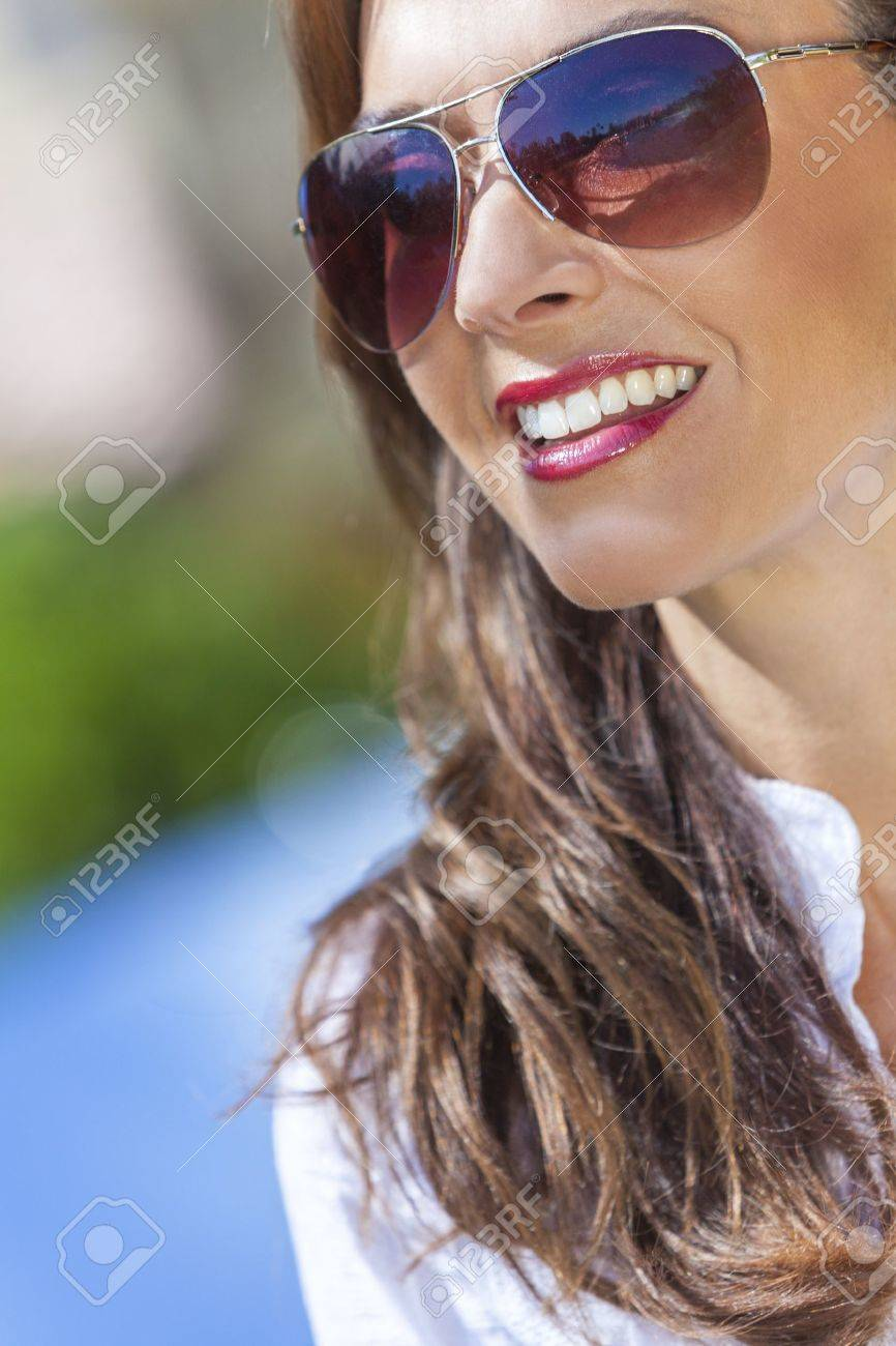 Outdoor portrait of a beautiful young brunette woman in her thirties wearing aviator style sunglasses Stock Photo - 17286191