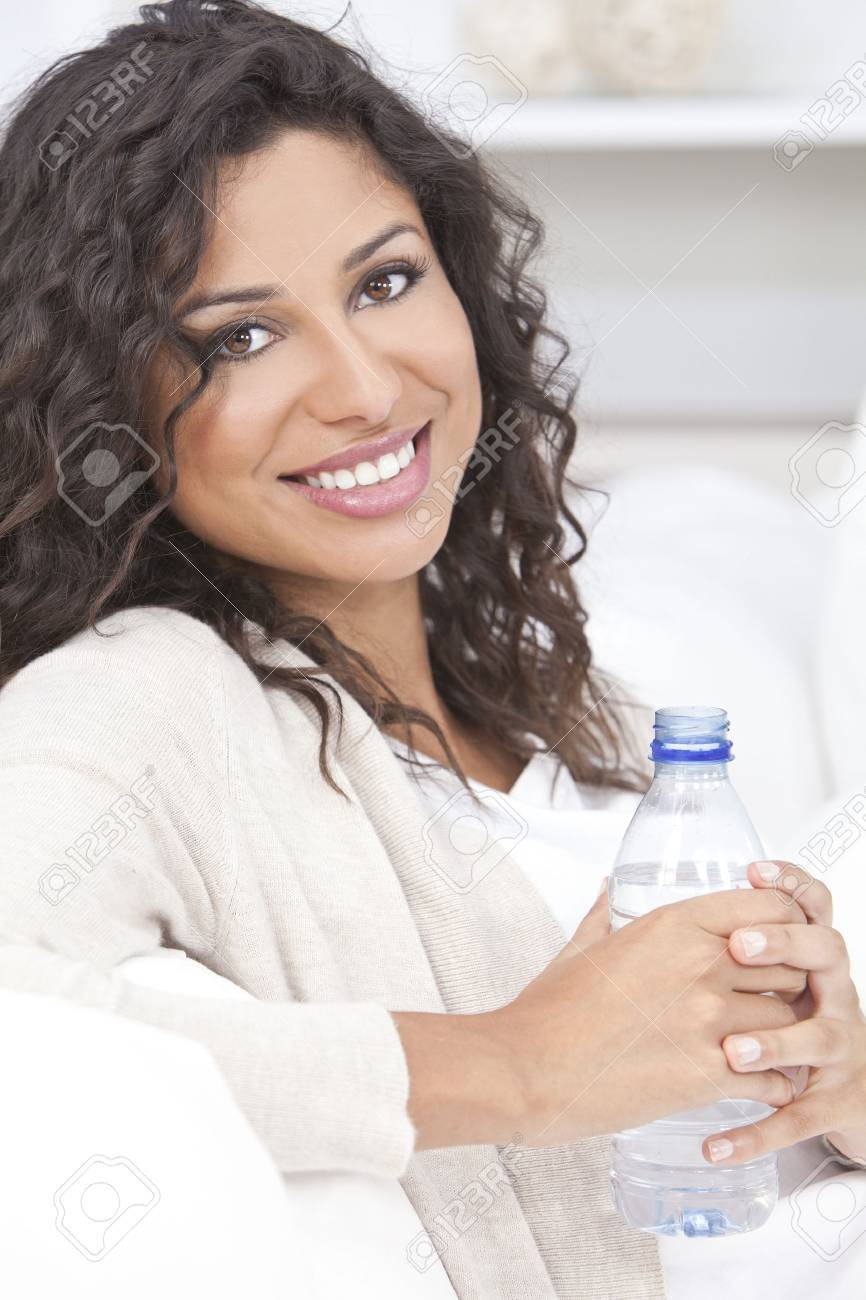 Beautiful young Latina Hispanic woman smiling, relaxing and drinking a bottle of water at home on a sofa Stock Photo - 17286179