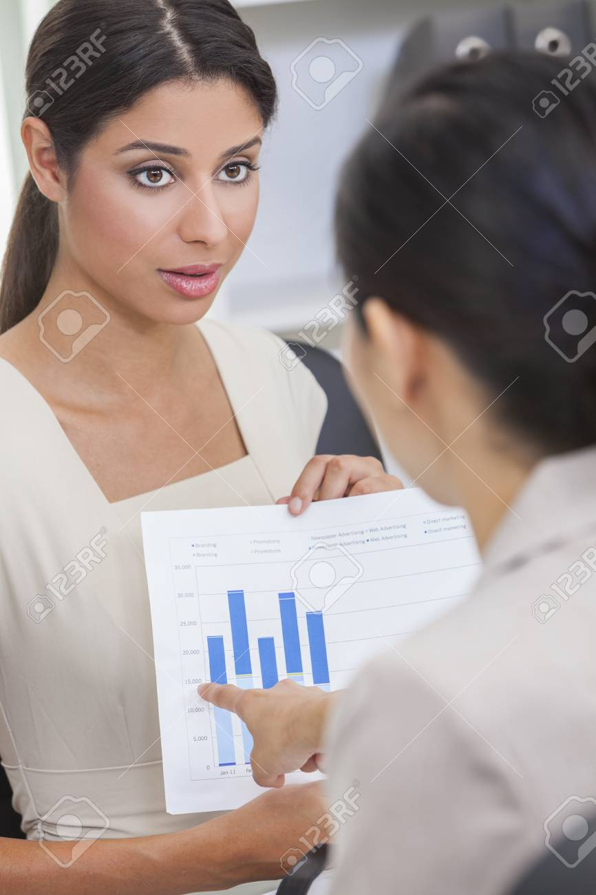 Portrait of a beautiful young mixed race Hispanic woman or businesswoman in office meeting with female colleague using a graph of figures or statistics Stock Photo - 17329572