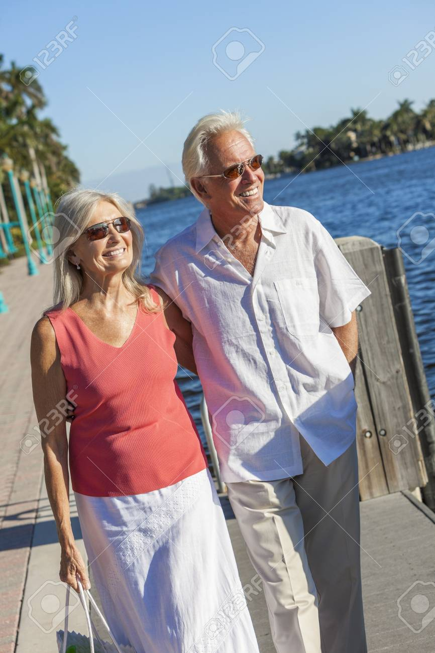 Happy senior man and woman romantic couple together looking out to tropical sea or river with bright clear blue sky Stock Photo - 17475679