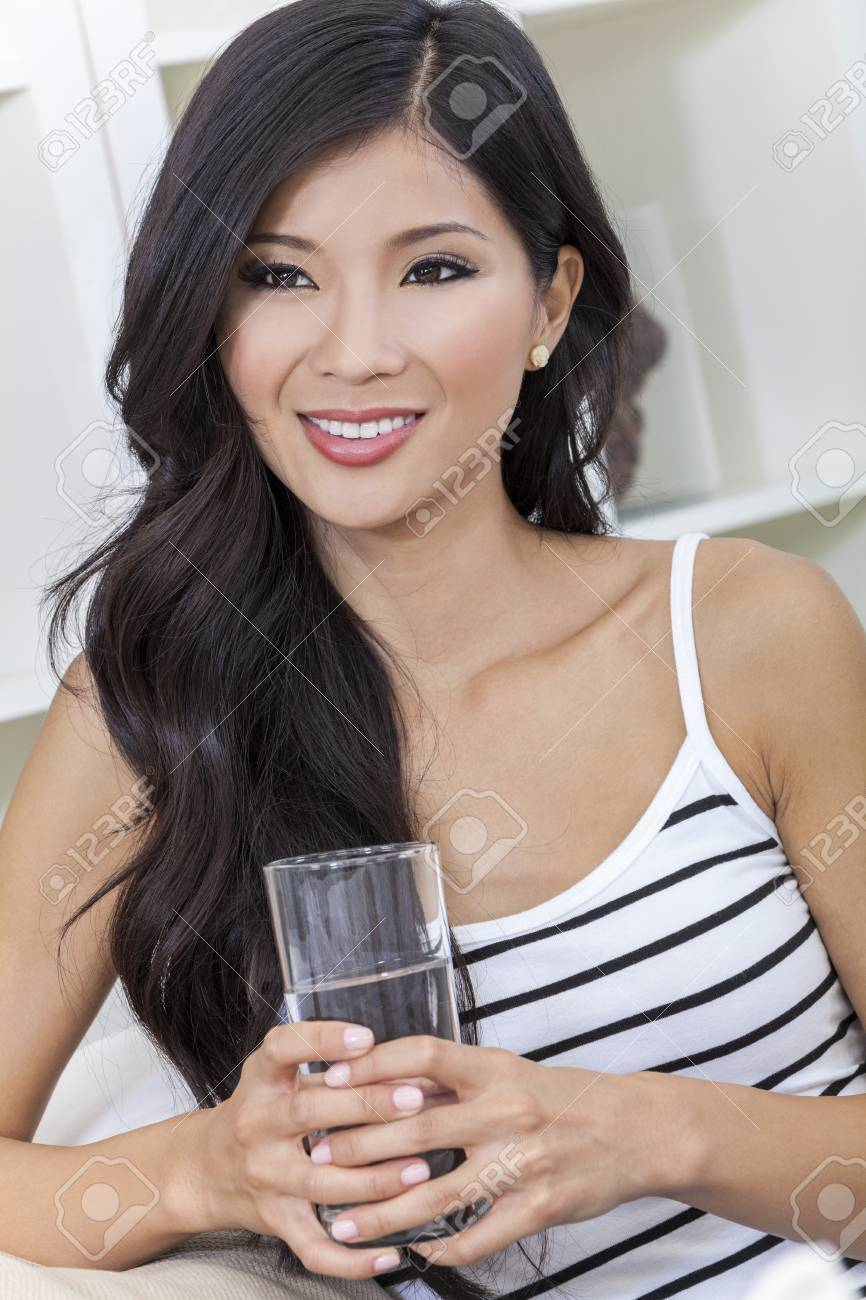 A beautiful happy young Chinese Asian Oriental woman with a wonderful toothy smile drinking a glass of water at home Stock Photo - 17544340