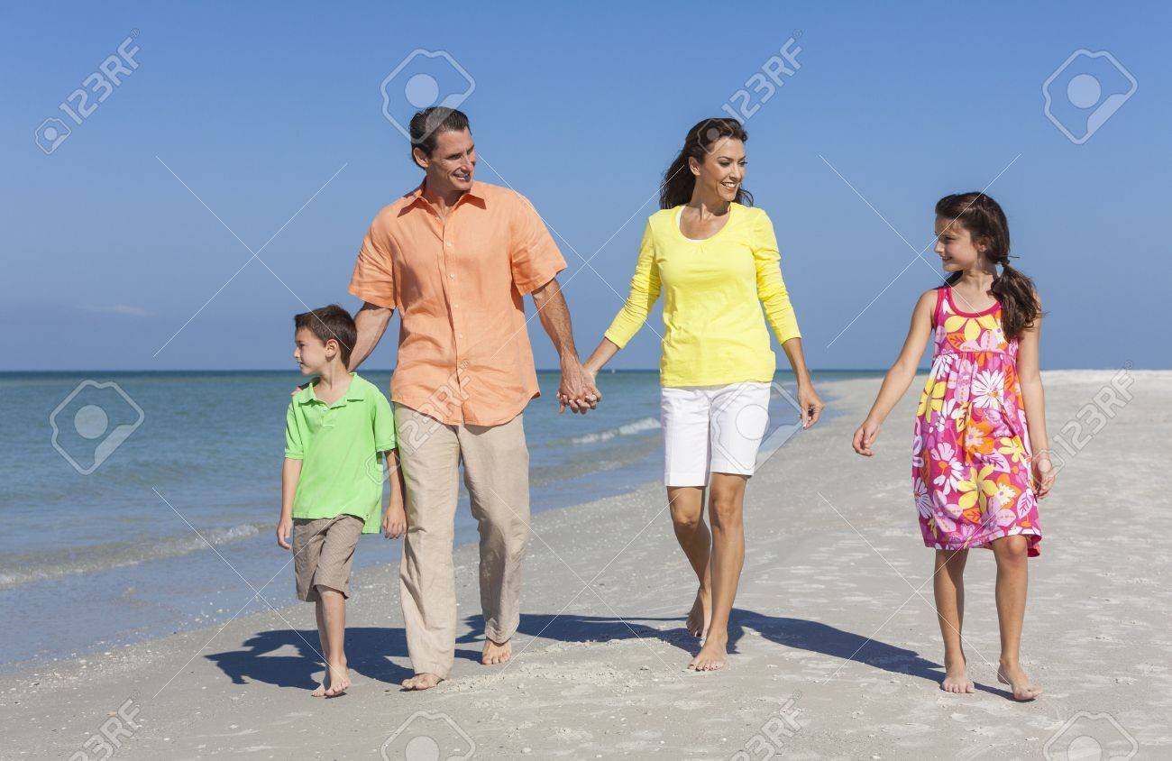 A happy family of mother, father and two children, son and daughter, walking holding hands and having fun in the sand of a deserted sunny beach Stock Photo - 17544335