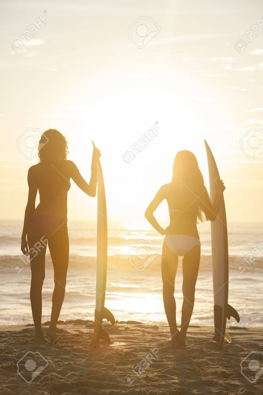 Rear view of two beautiful sexy young woman surfer girls in bikinis with white surfboards on a beach at sunset or sunrise Stock Photo - 17758188