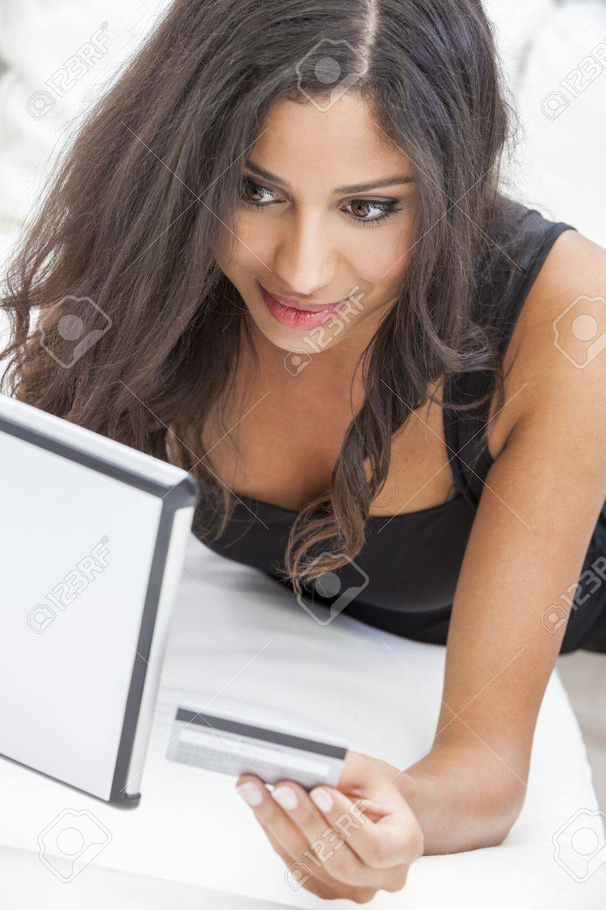 Beautiful mixed race Hispanic Latina woman using a credit card to shop on line using the internet and a tablet computer Stock Photo - 17758201