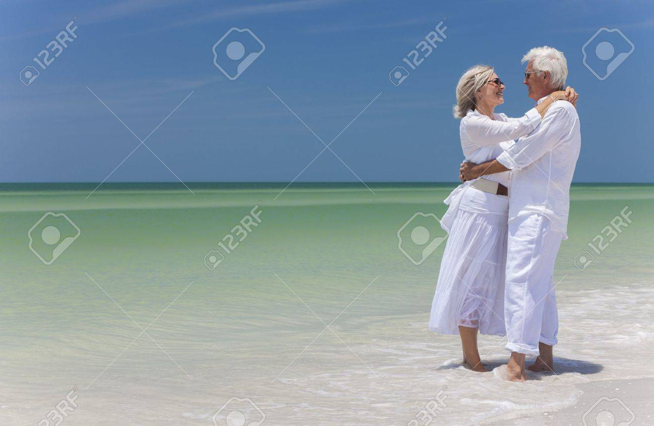 Happy senior man and woman couple together embracing by sea on a deserted tropical beach with bright clear blue sky Stock Photo - 17862046