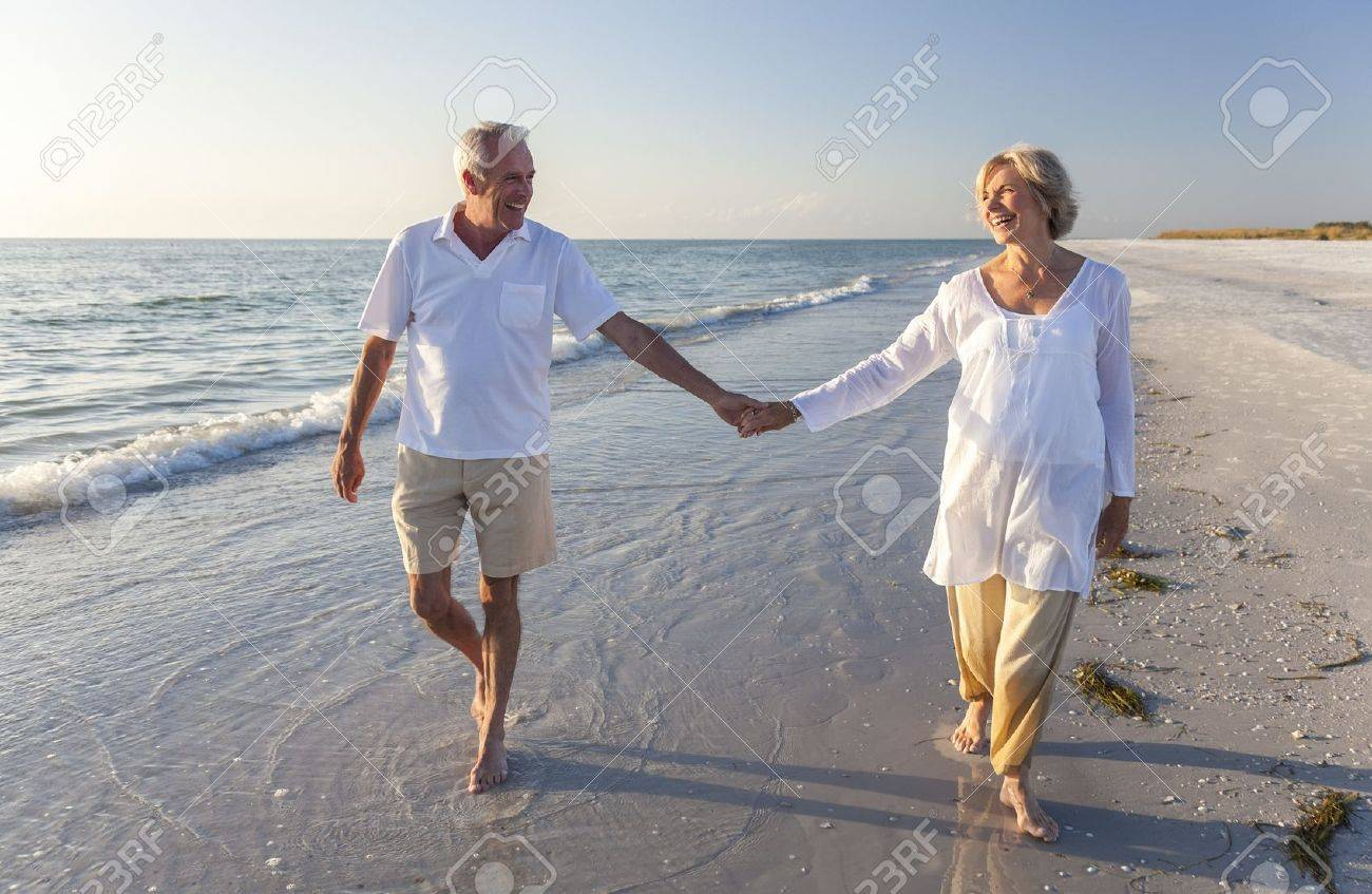 Happy senior man and woman couple walking and holding hands on a deserted tropical beach with bright clear blue sky Stock Photo - 18316816