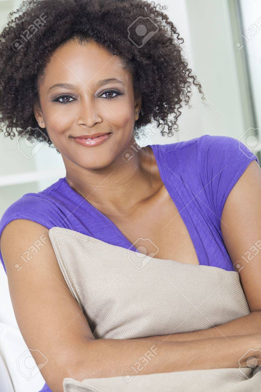 A beautiful mixed race African American girl or young woman looking happy and thoughtful holding a cushion Stock Photo - 19285130