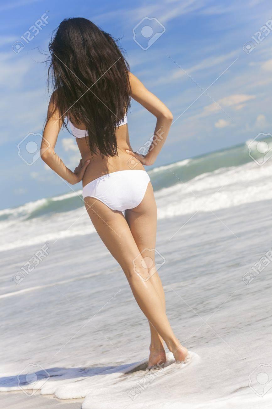 Vista Trasera De Una Joven Mujer Morena Sexy O Niña Que Llevaba Un Bikini  Blanco De Pie En El Surf En Una Playa Tropical Desierta Con Un Cielo Azul  Fotos, Retratos, Imágenes
