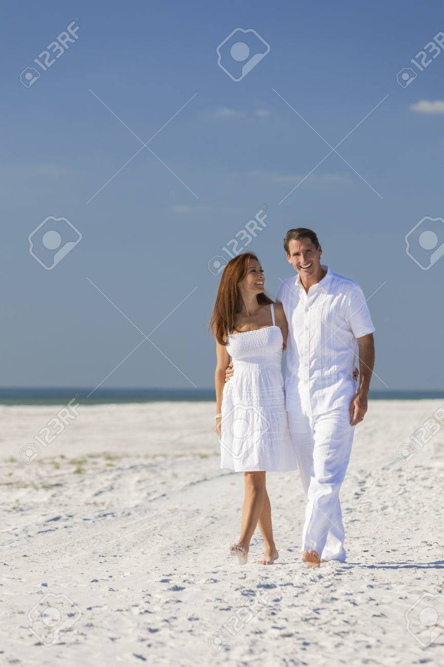 b25f86f0aca3 Romantic man and woman romantic couple in white clothes walking on a deserted  tropical beach with