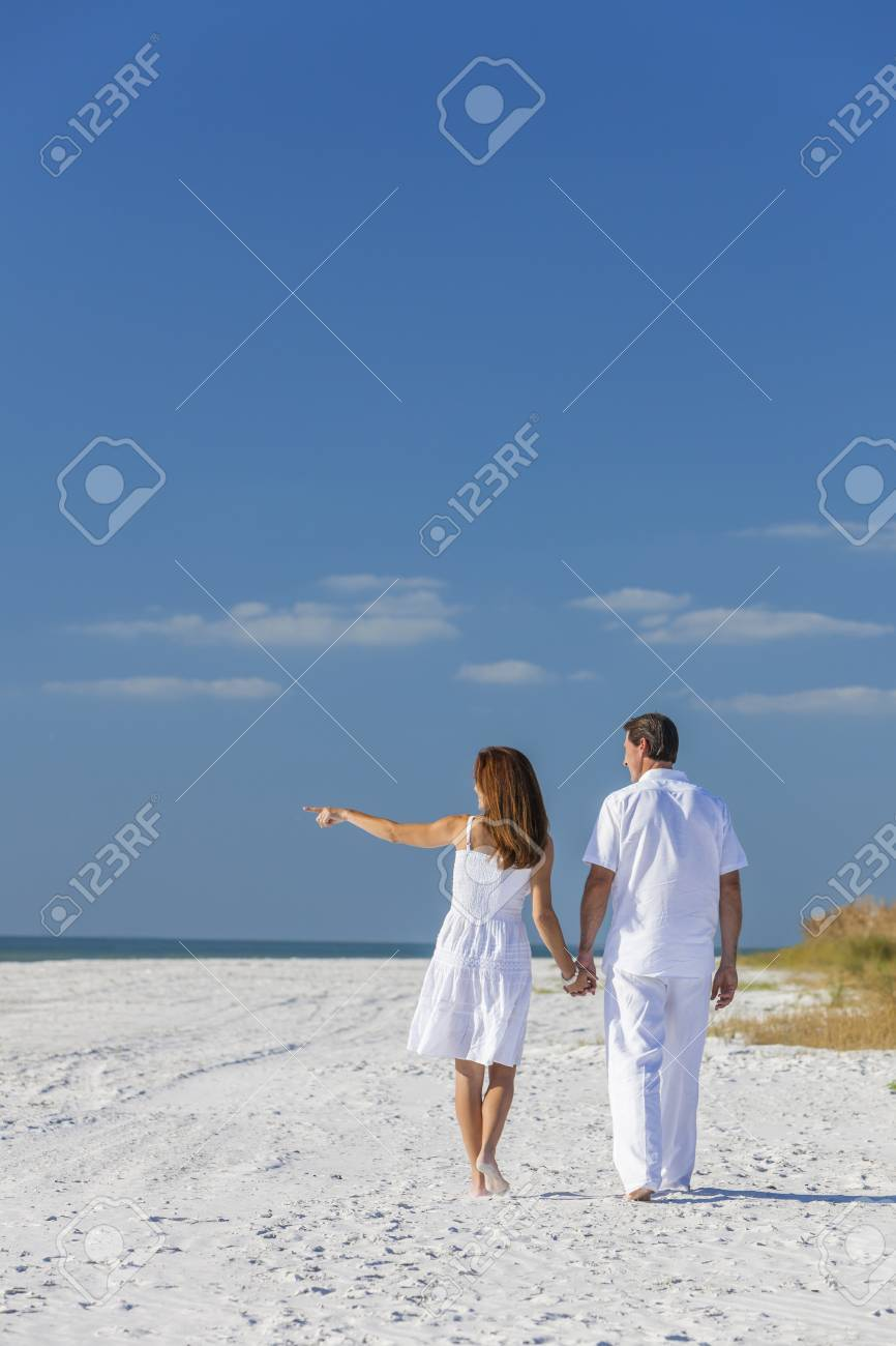 4bb7b1f21980 ... deserted tropical beach with bright clear blue sky. Rear view of man  and woman romantic couple in white clothes walking holding hands and  pointing