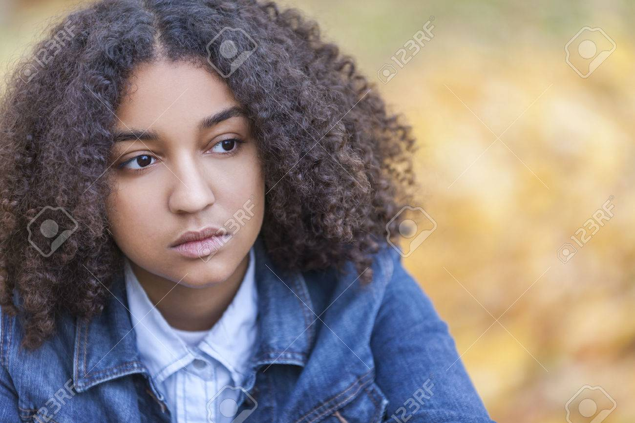 Beautiful mixed race African American girl teenager female young woman outside in autumn or fall looking sad depressed or thoughtful - 50404403