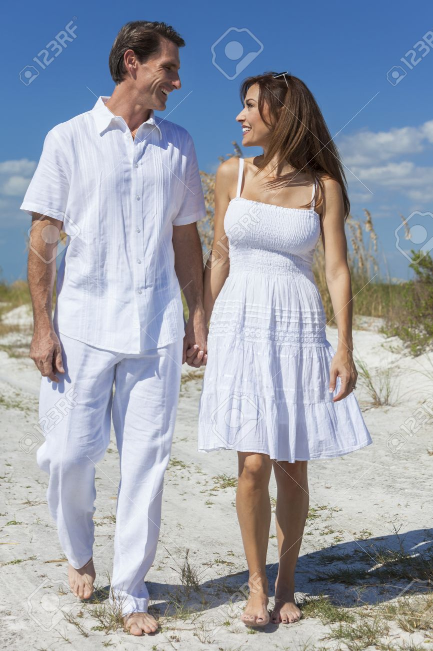 1d1f1bf0877a Middle aged man and woman romantic couple in white clothes walking on a deserted  tropical beach