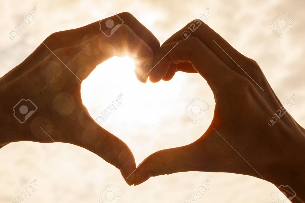 Hand heart shape silhouette made against the sun & sky of a sunrise or sunset - 70751214
