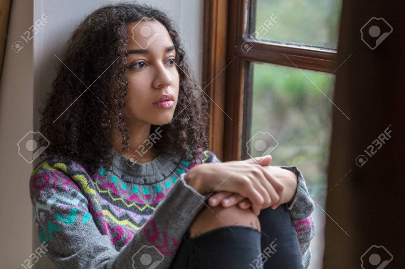 Beautiful mixed race African American girl teenager female young woman sad depressed or thoughtful looking out of a window - 69903140