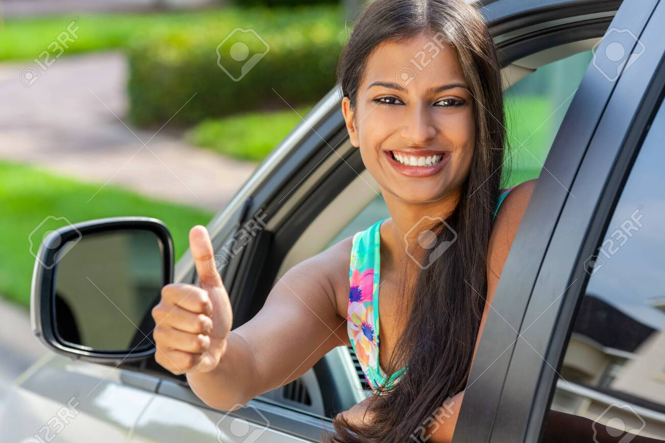 Beautiful Indian Asian young woman or girl leaning out of a car giving a thumbs up in summer sunshine smiling with perfect teeth and long hair. Car hire, driving test concept. - 125618173
