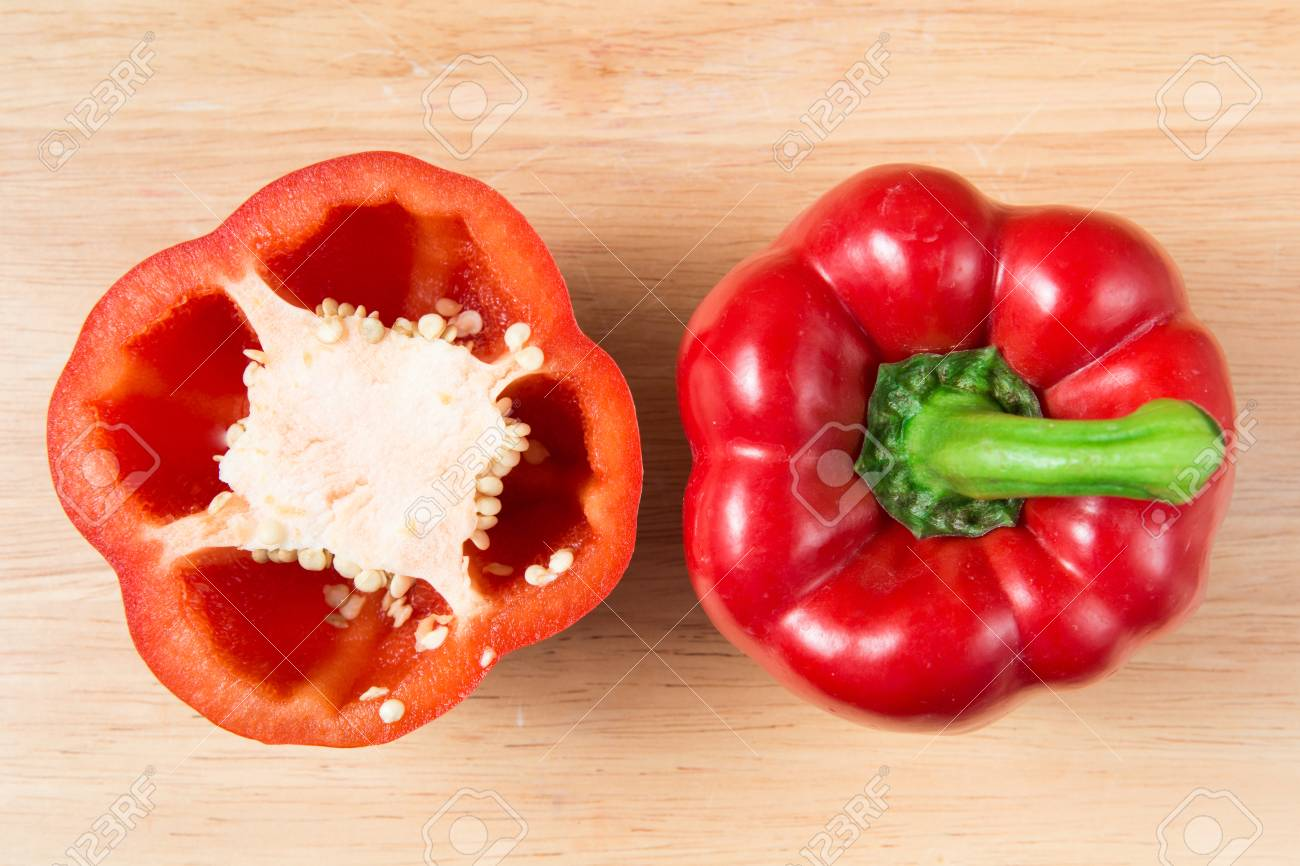 red sweet pepper and a half on a wooden block - 66752085