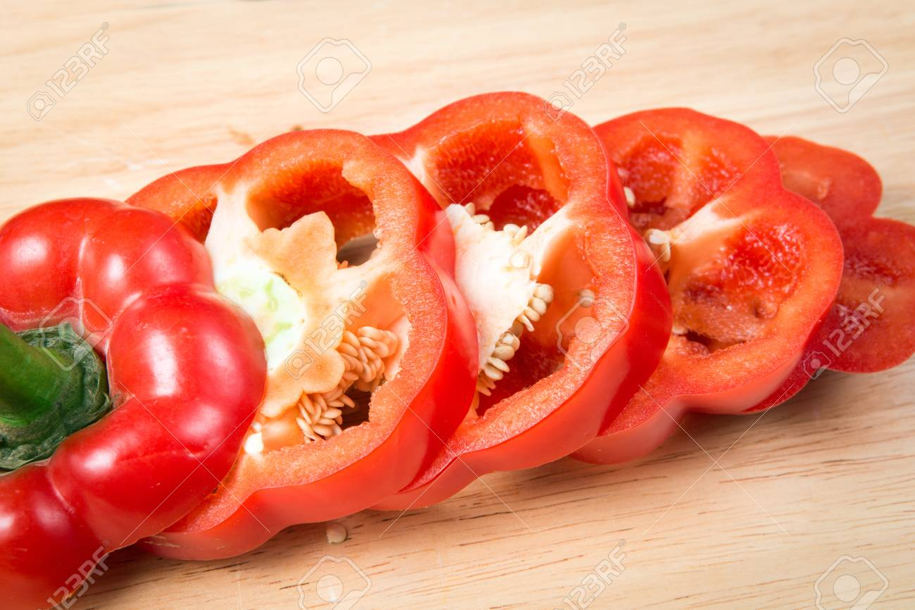 sliced red sweet pepper on a wooden block - 66557608