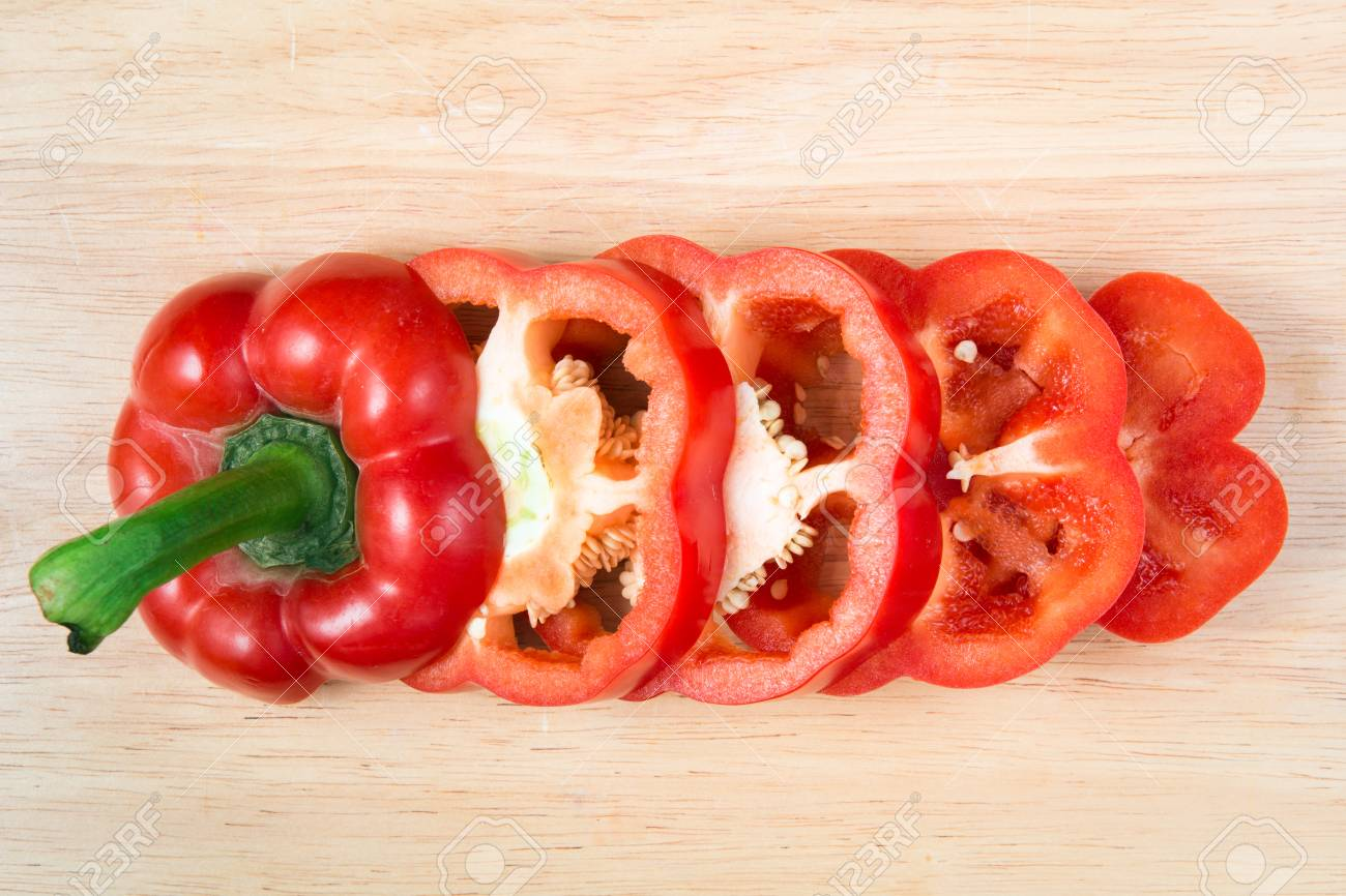 sliced red sweet pepper on a wooden block - 67147951