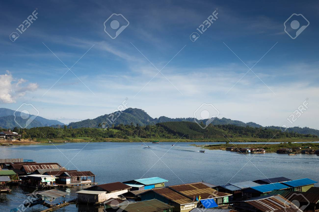 Landscape view of great lagoon in front of a mountain with a village on bottom and a blue sky - 67273471
