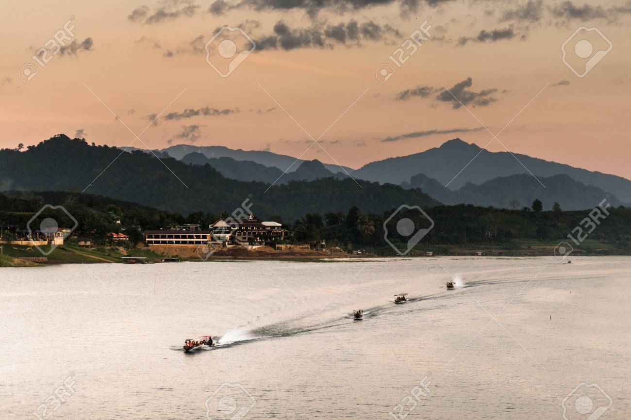 landscape view of great lagoon with four of boats downstream along a lagoon with a mountain behind in an evening. - 67339072