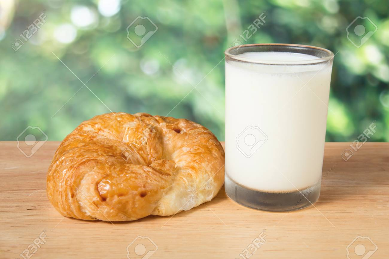 butter croissant and a glass of milk on a wooden block - 67698445