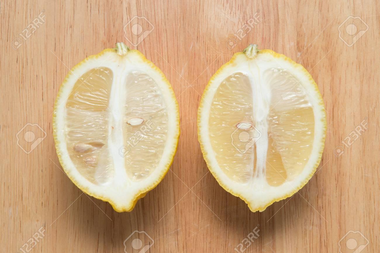 sliced lemon fruit on a wooden block - 71400171