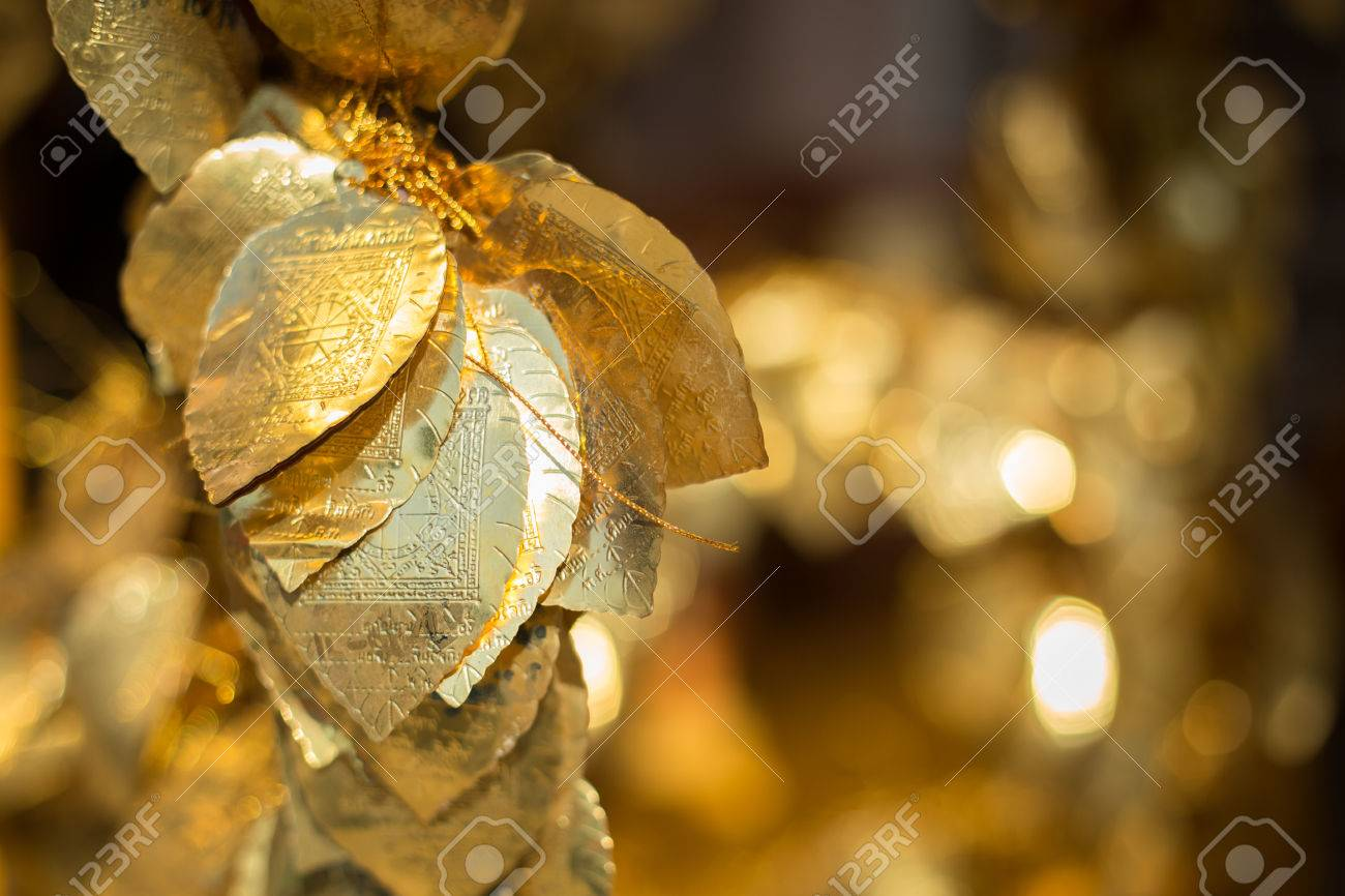 Golden Bodhi leaf. A Buddha charm in a blurry background.Selective focus - 71400170