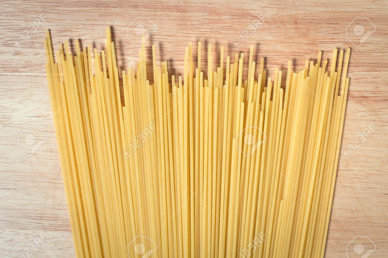 pile of raw spaghetti on a wooden block - 79022369