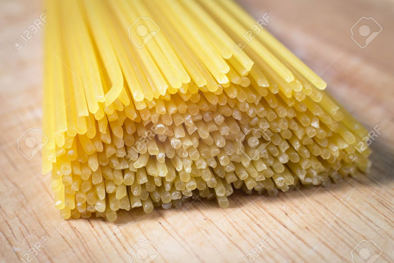 pile of raw spaghetti on a wooden block - 79022370