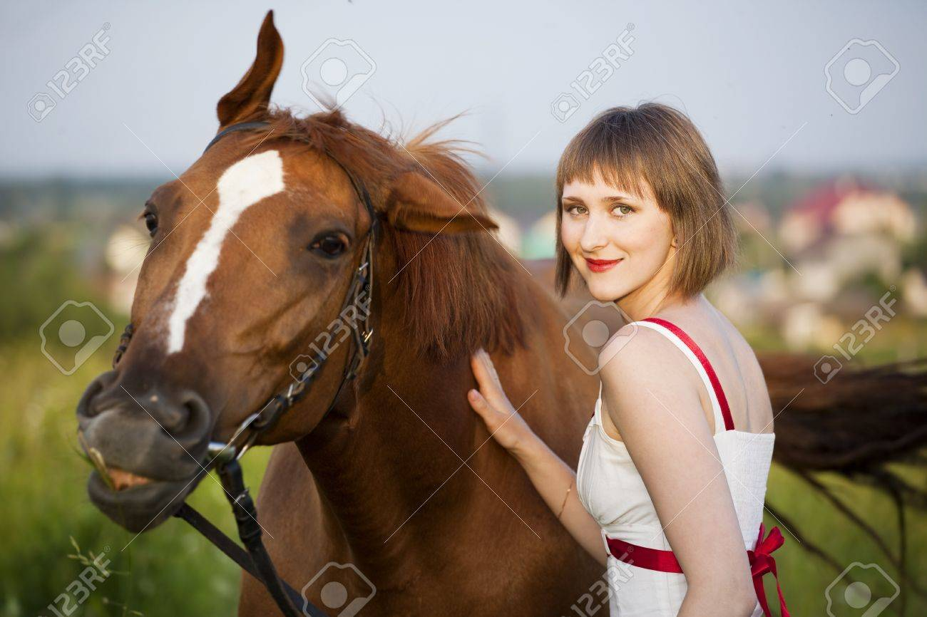 young woman with horse in the field Stock Photo - 7755548