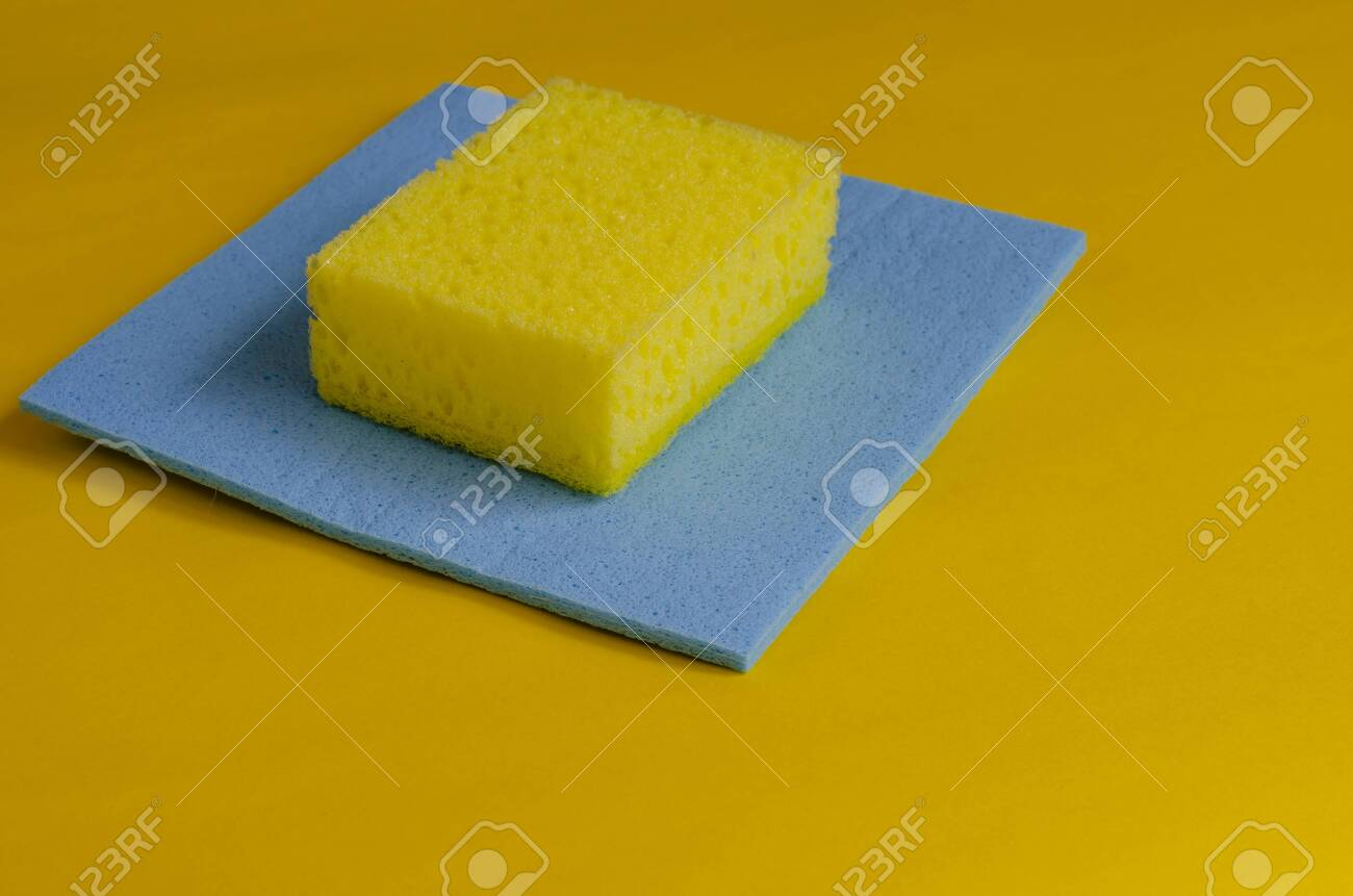 Kitchen sponge and blue cleaning napkin on yellow. Accessories for washing dishes and cleaning. Commercial cleaning company. Selective focus. Close-up. - 145087130