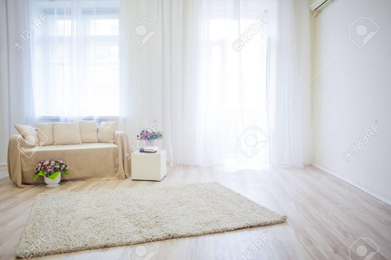 Chambre blanche canapé beige livres et fleurs 1