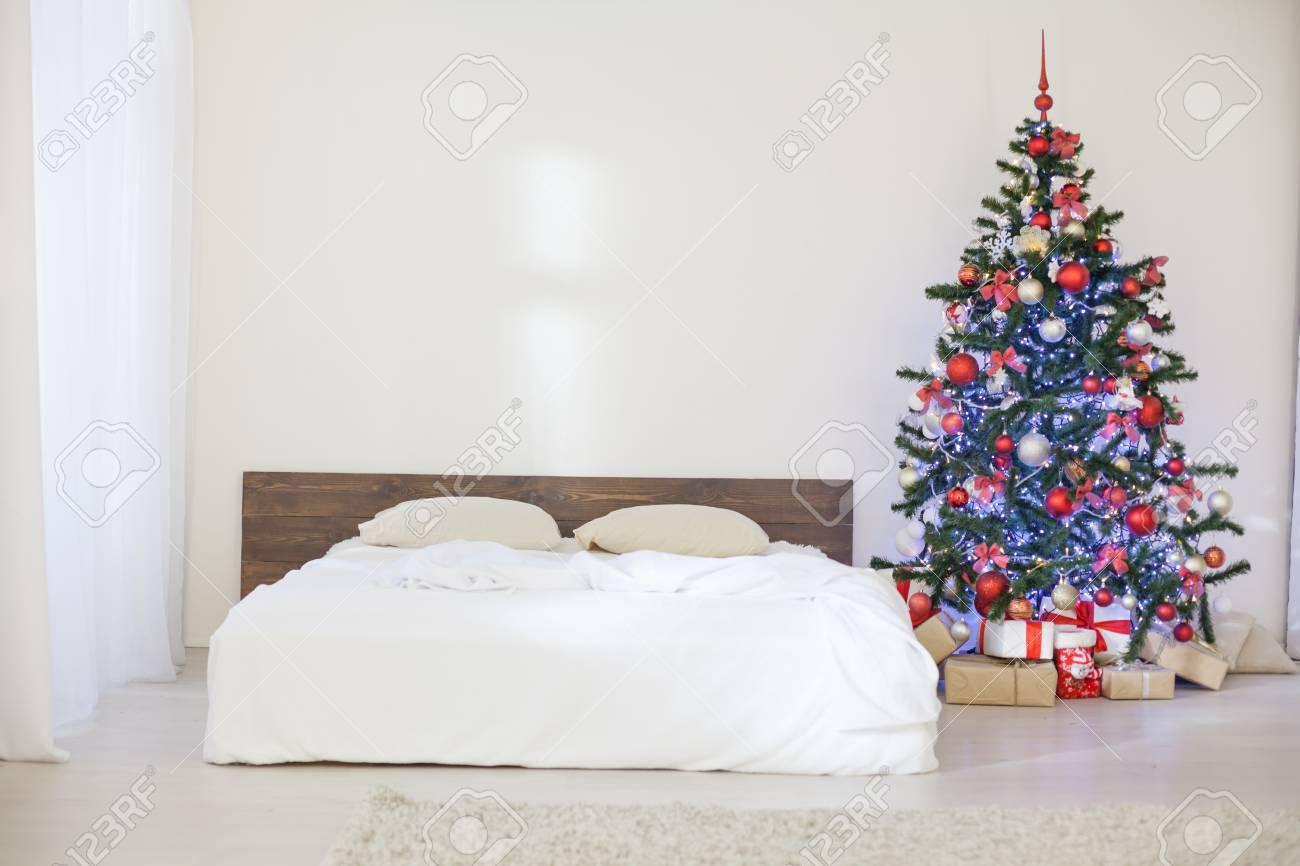 Arredamento camera da letto bianca con albero di Natale regali di Natale