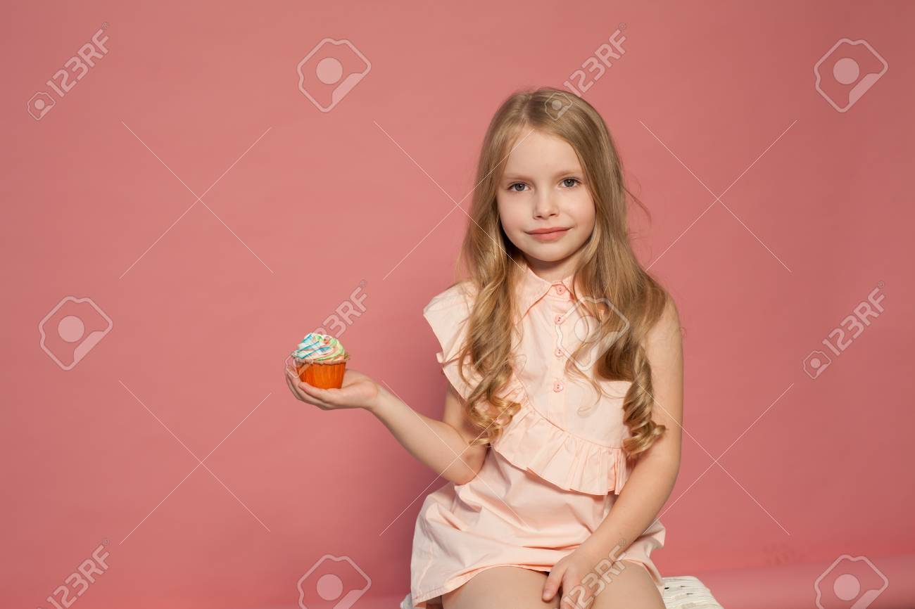 small girl in hand holds a sweet cupcake cake candy - 114079465