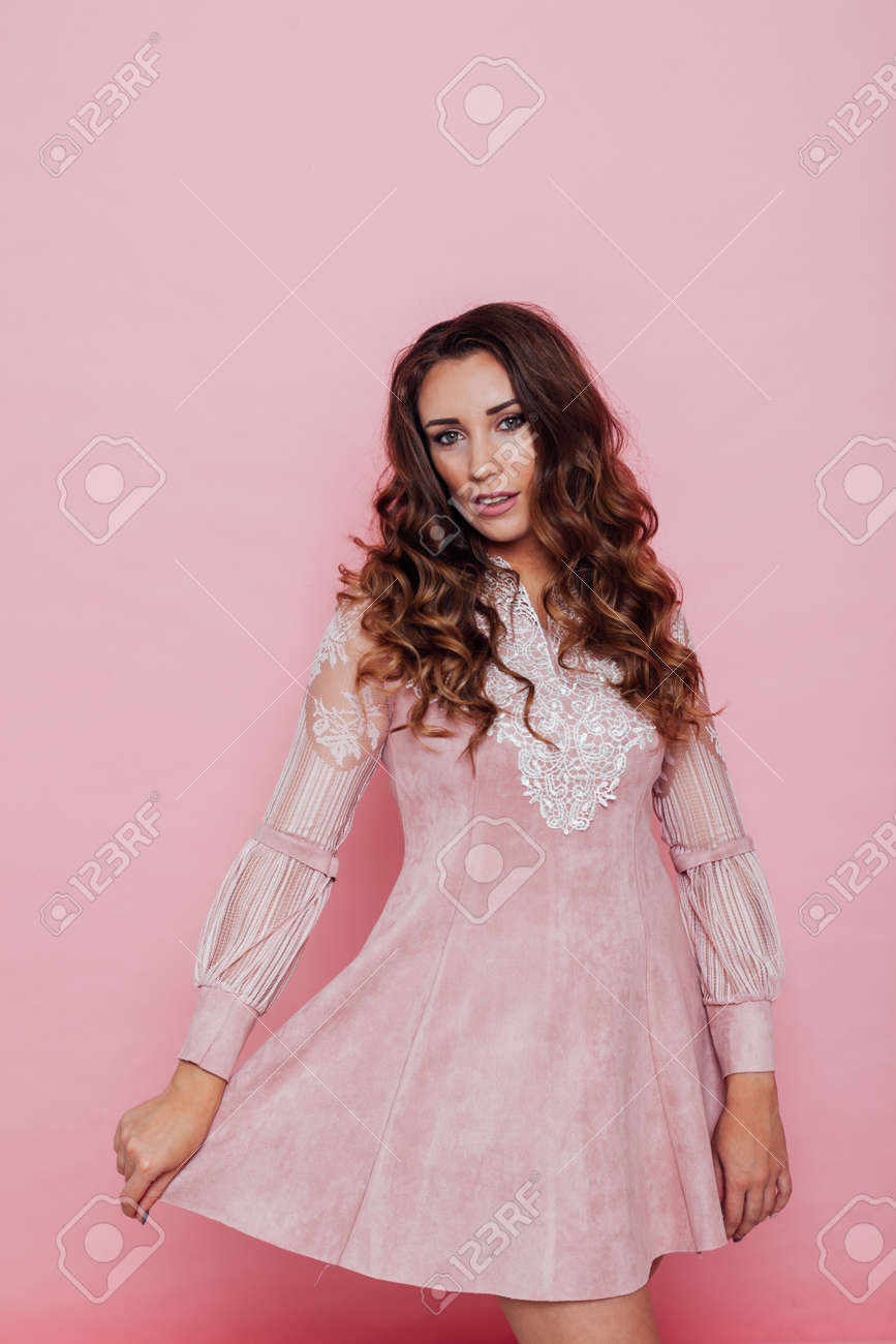 Portrait of a beautiful fashionable woman with curls in a pink dress - 133511361