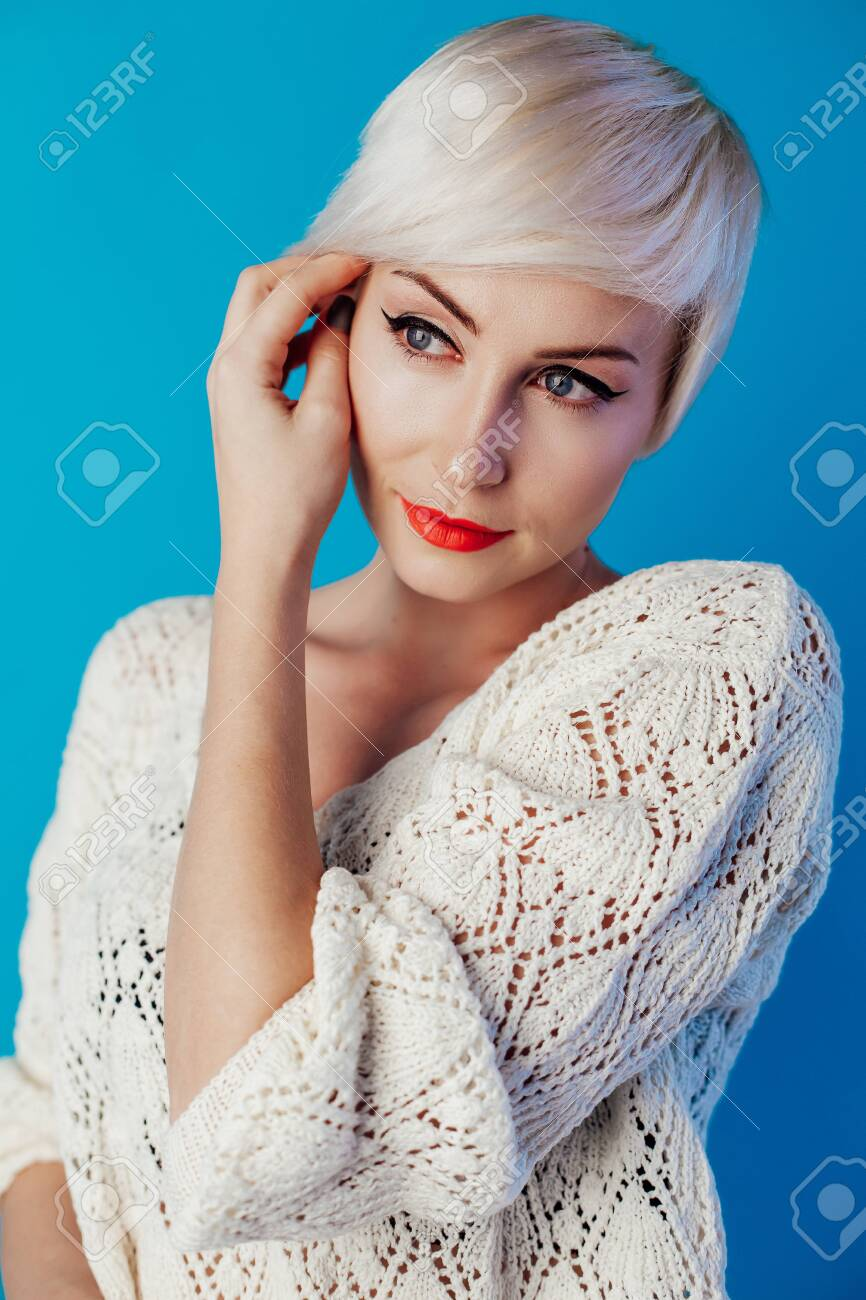 Portrait of blonde with short hair on a blue background - 134880566