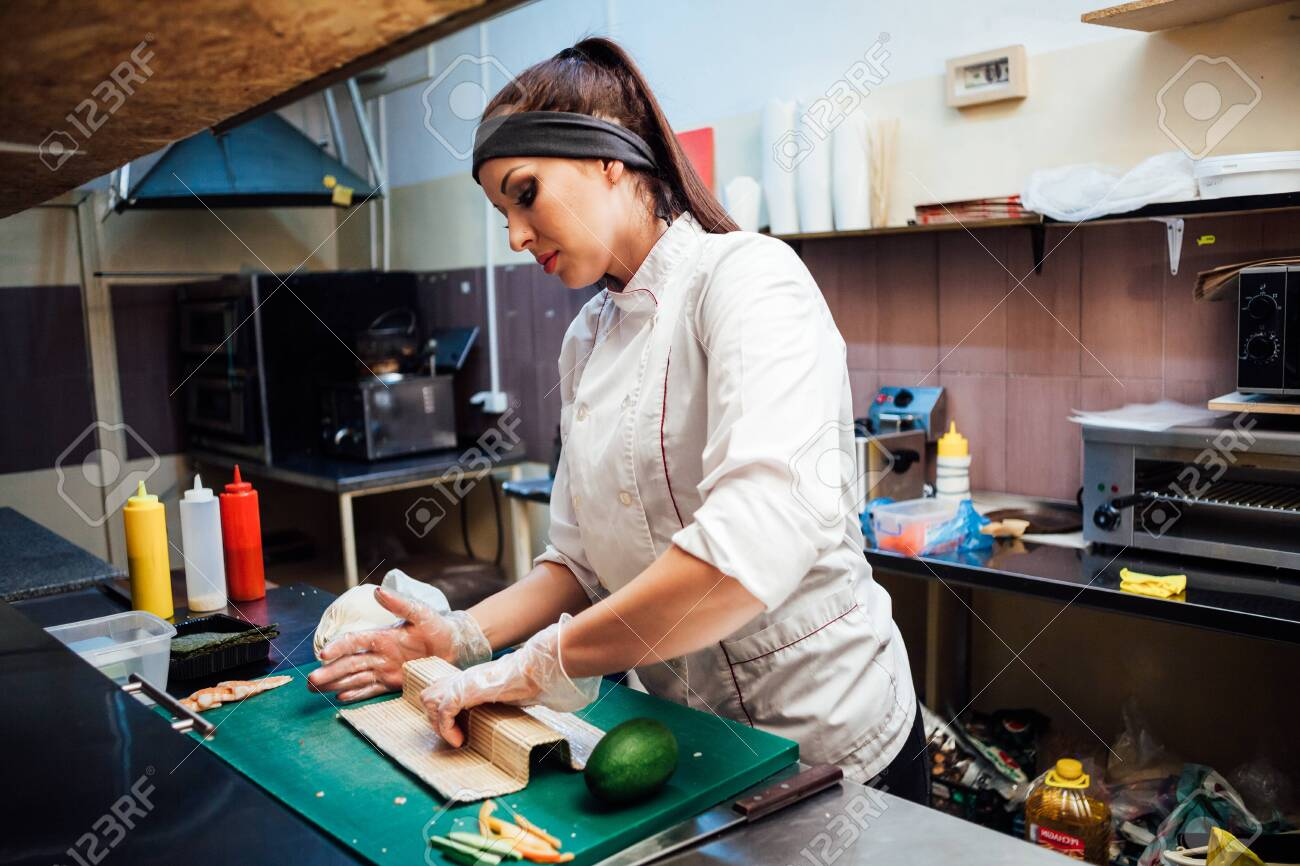 woman chef prepares fresh sushi in the kitchen of the restaurant - 136614080