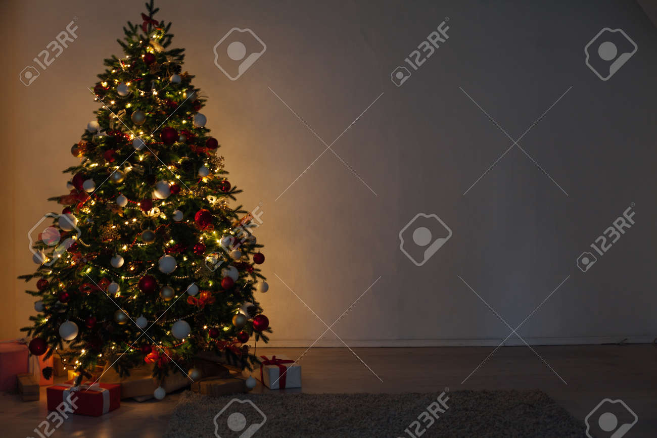 Christmas tree with gifts of garland lights at night on New Years Eve in the interior room - 158984947