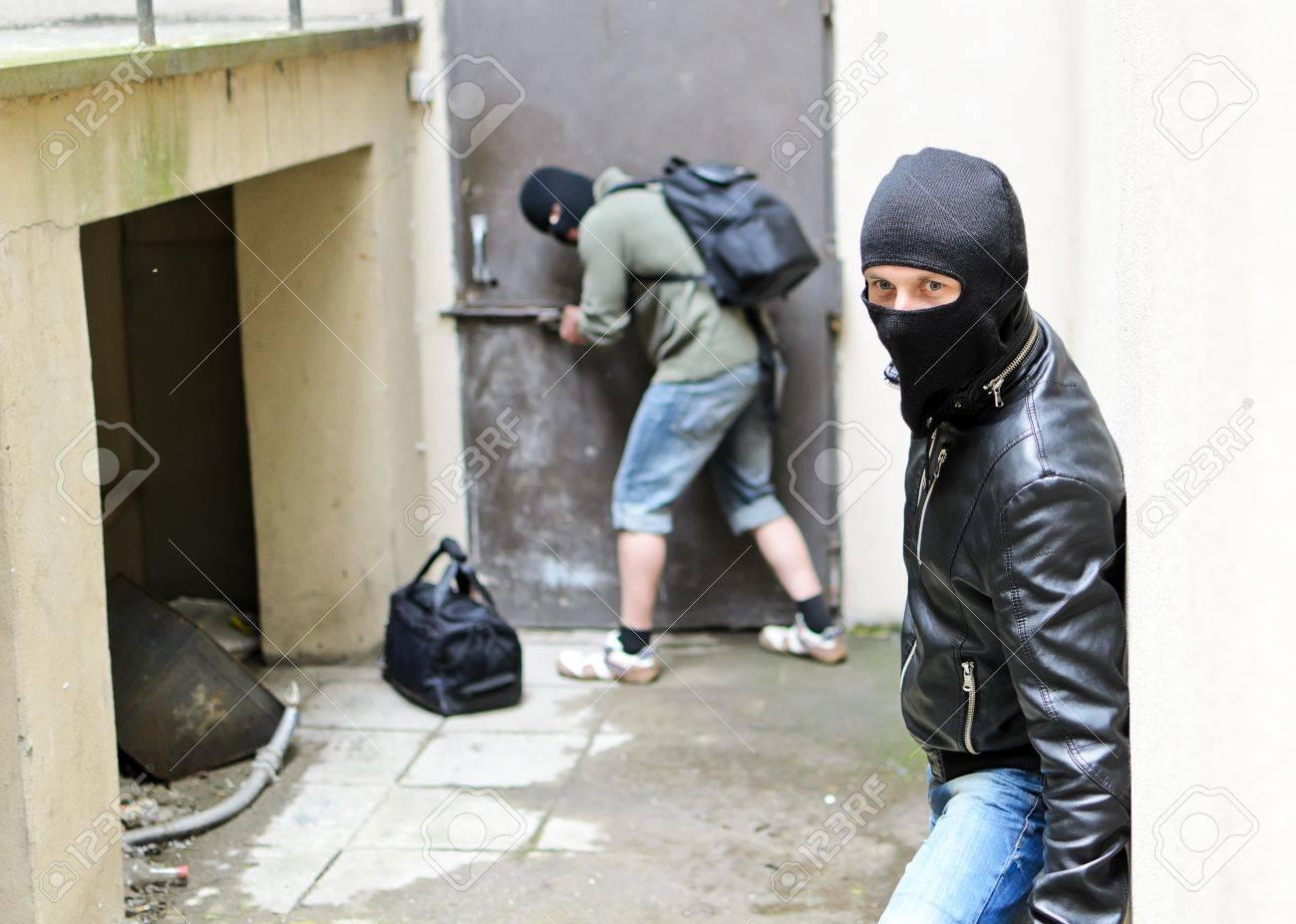 Burglary  One burglar tries open the door  Second is on the lookout Stock Photo - 13559114