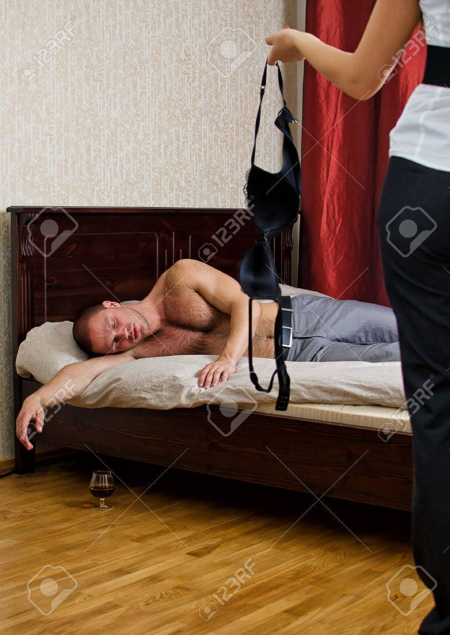 Betrayal concept: wife with a stranger bra and drunken husband in bed Stock Photo - 14427696