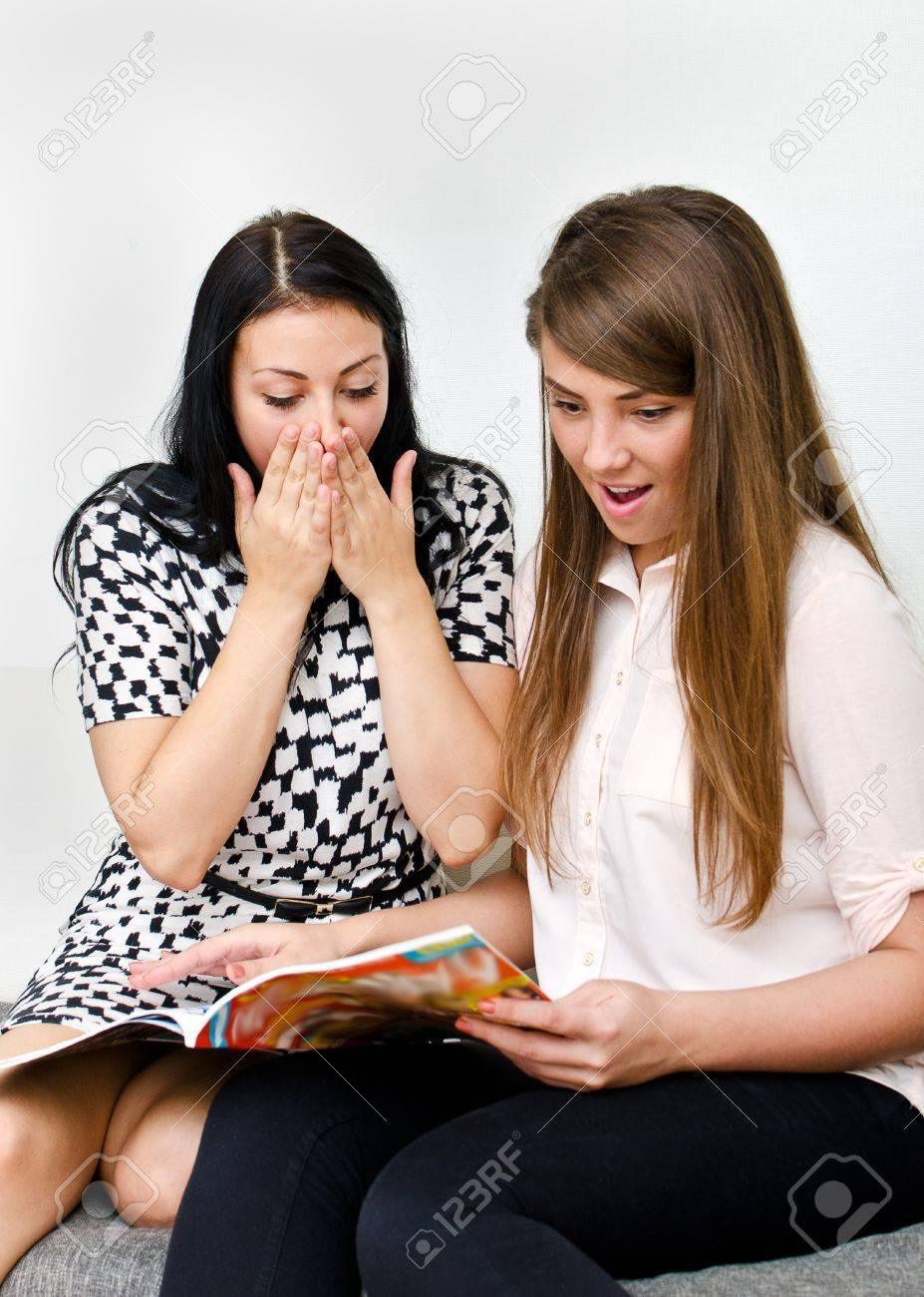 Two pretty girls reading magazine on the sofa Stock Photo - 15303707